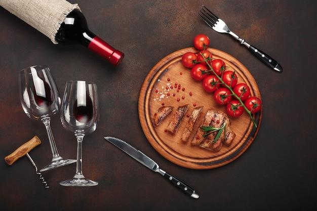 Bistecche di maiale alla griglia a fette con bottiglia di vino, bicchiere di vino, cavatappi, coltello, forchetta, pane nero, pomodorini e rosmarino su sfondo arrugginito