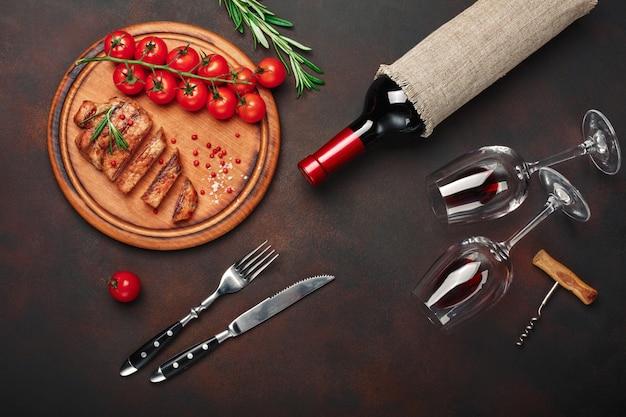 Bistecche di maiale alla griglia a fette con bottiglia di vino, bicchiere di vino, cavatappi, coltello, forchetta, pane nero, pomodorini