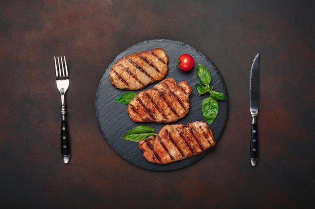 Bistecche di maiale alla griglia con basilico, pomodori, coltello e forchetta su pietra nera e sfondo marrone arrugginito