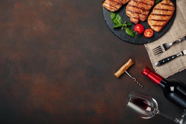 Bistecche di maiale alla griglia su pietra con bottiglia di vino, bicchiere di vino, coltello e forchetta su sfondo arrugginito