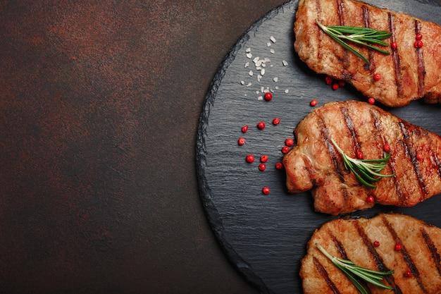 Bistecche di maiale alla griglia su pietra con rosmarino e rad pepper su sfondo arrugginito