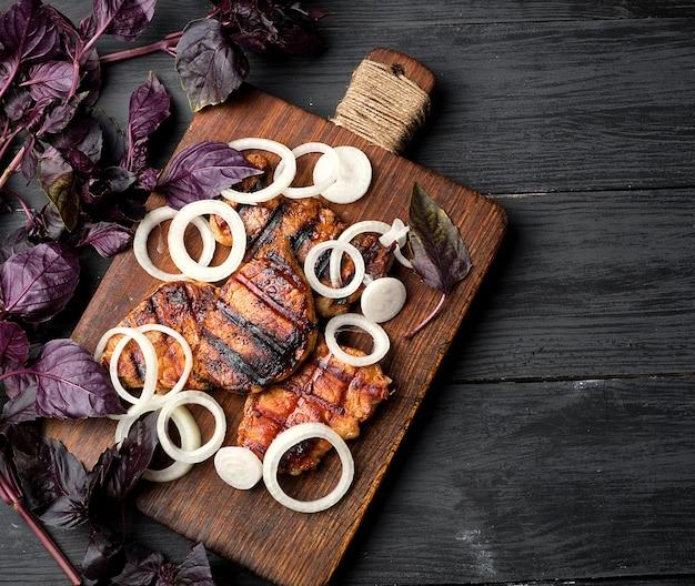 Bistecche di maiale alla griglia succose su una tavola di legno marrone