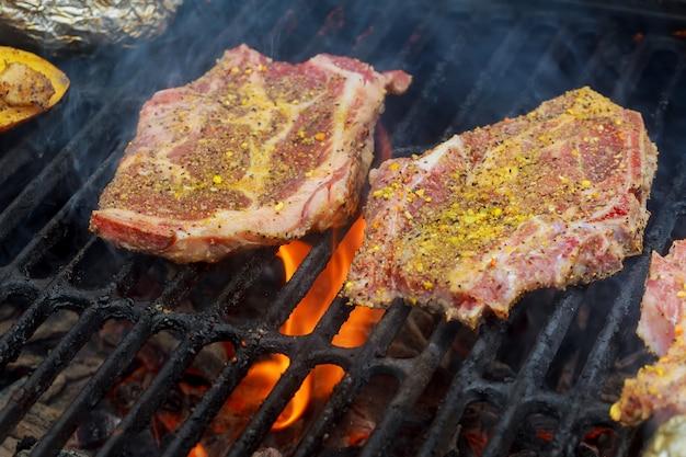 Bistecche di maiale alla griglia sulla griglia