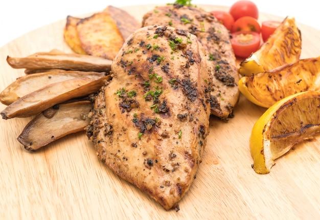 Bistecche di pollo alla griglia con verdure sul bordo di legno