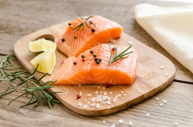 Bistecche di salmone crude sulla tavola di legno