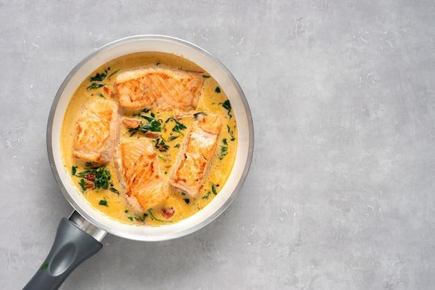 Bistecche di salmone deliziose in salsa di panna su luce
