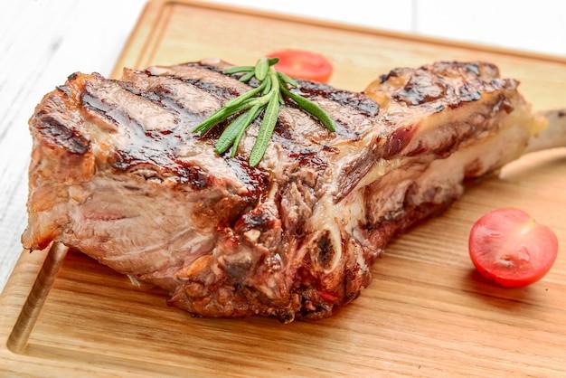 Bistecche di tomahawk appena grigliate su tavola di legno