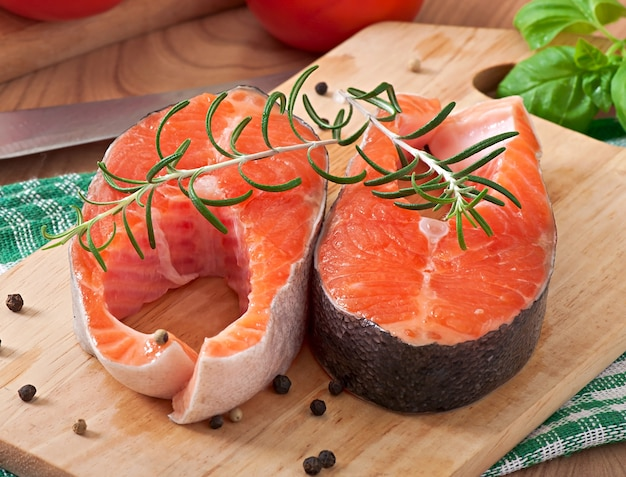 Bistecche fresche e crude trota su un tagliere di legno con fette di limone, rosmarino e pepe