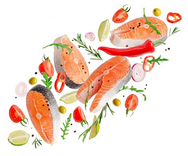 Bistecche grezze di salmone pesce che vola con spezie ed erbe isolate