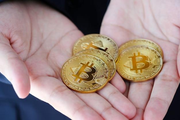 Bitcions nel concetto della mano, della criptovaluta e della blockchain dell'uomo d'affari