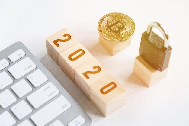Bitcoin con numeri sui cubi su un fondo di legno bianco con una tastiera e una serratura.