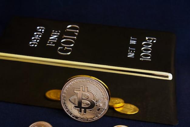 Bitcoin criptovaluta e lingotti d'oro su sfondo nero.