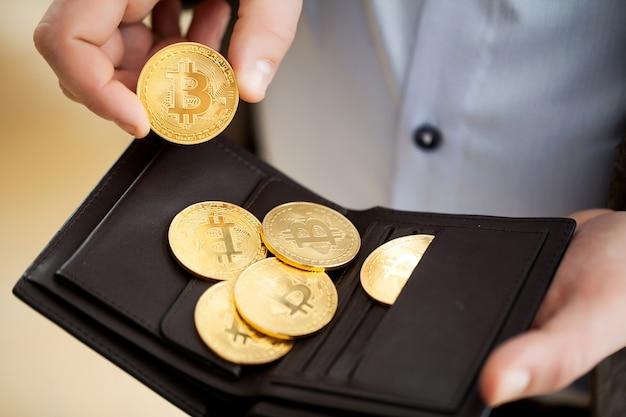 Bitcoin d'oro monete nelle mani dell'uomo