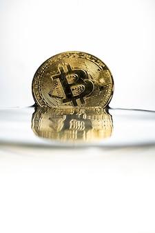 Bitcoin dell'oro con spruzzata dell'acqua su priorità bassa bianca