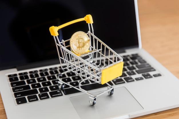 Bitcoin di criptovaluta in mini carrello del supermercato sul computer portatile