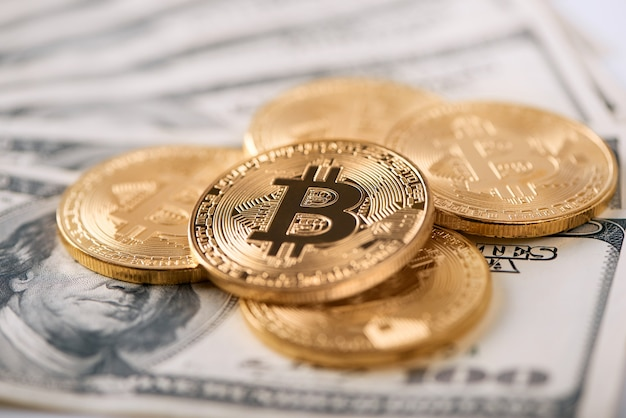 Bitcoin dorati cifrati che presentano la più grande criptovaluta mondiale al giorno d'oggi che si trovano su vecchie banconote da cento dollari.