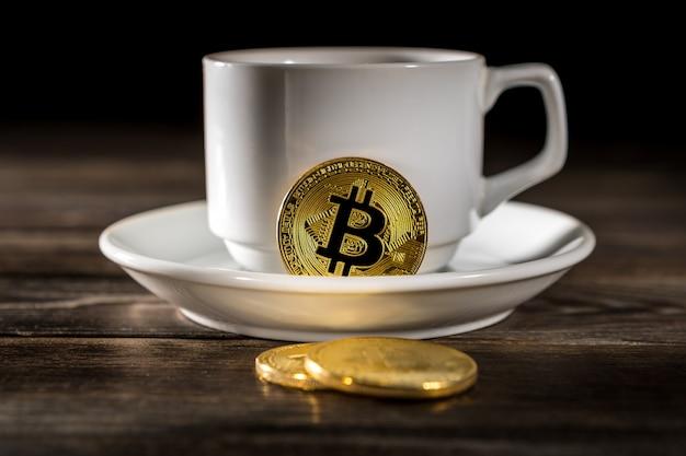 Bitcoin dorato di criptovaluta che sta sulla tazza di caffè isolata