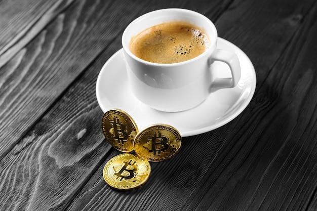 Bitcoin dorato di criptovaluta che sta sulla tazza di caffè