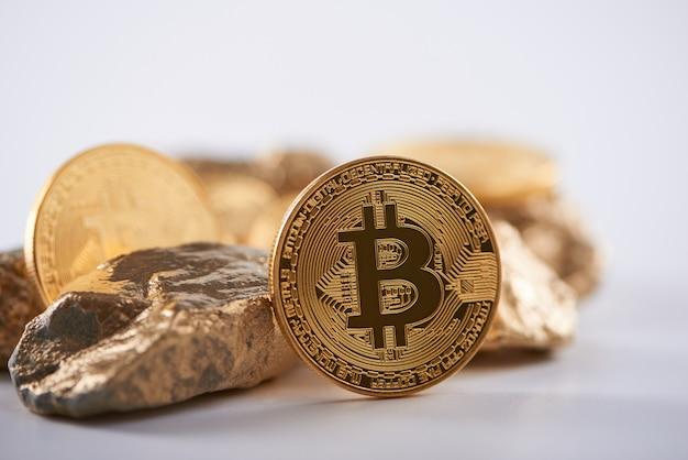 Bitcoin dorato lucido accanto a grumi d'oro