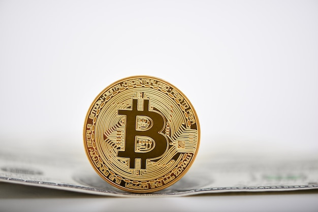 Bitcoin dorato presentato su una banconota da un dollaro come la più importante criptovaluta mondiale.