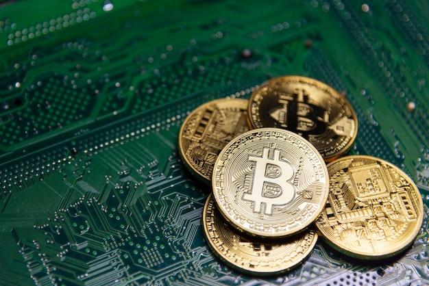 Bitcoin dorato su scheda madre verde.
