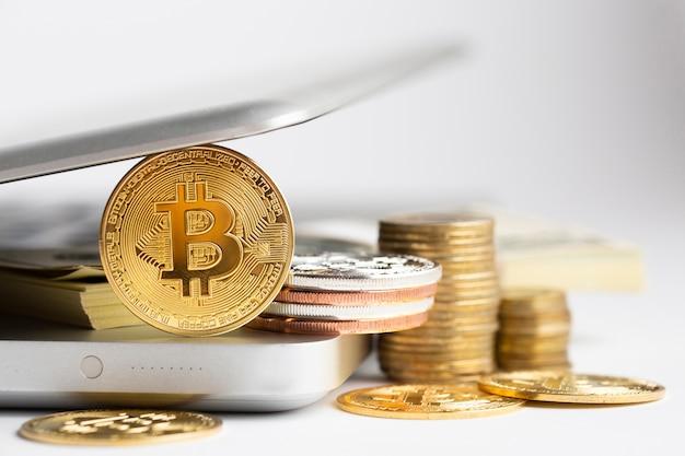 Bitcoin e pila di banconote sul computer portatile defocused