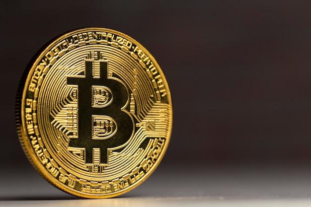 Bitcoin fisico in piedi a un tavolo bianco davanti a un muro di mattoni