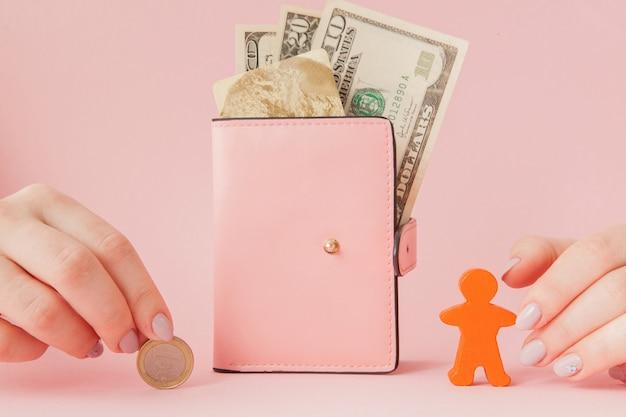 Bitcoin in mano di una donna e dollari in portafoglio rosa con carta di credito su uno sfondo rosa