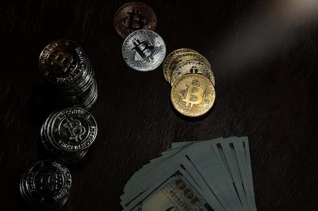 Bitcoin oro argento e rame impilati tra le altre monete e banconote