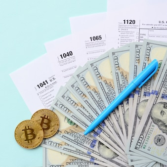 Bitcoin si trova con i moduli fiscali e centinaia di banconote da un dollaro su uno sfondo azzurro. dichiarazione dei redditi