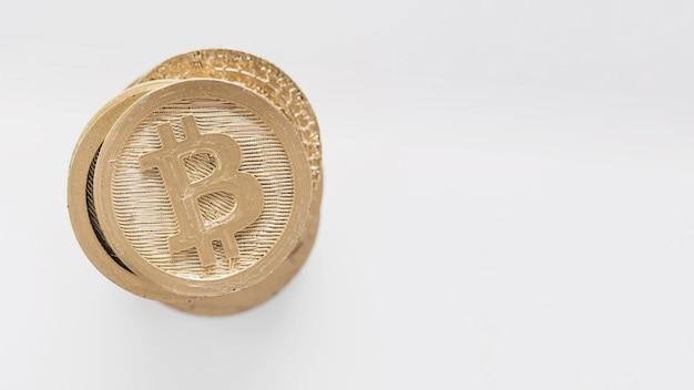 Bitcoins dorati impilati su fondo bianco