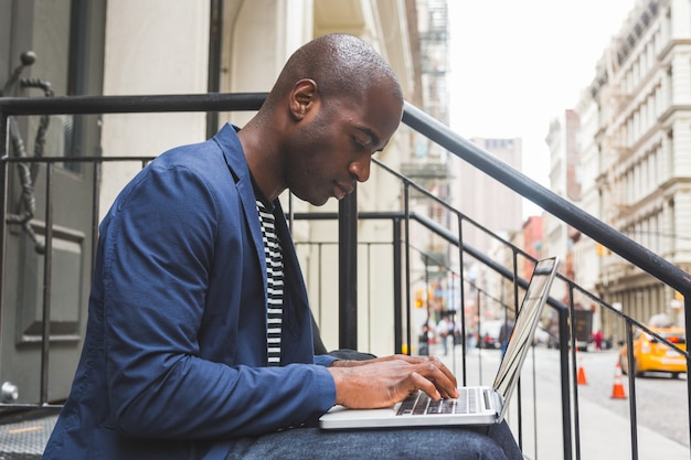 Black guy using notebook a new york