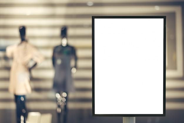 Blank mock up del segno di cartellone pubblicitario verticale con spazio di copia per il tuo messaggio di testo o contenuto nel centro commerciale moderno.