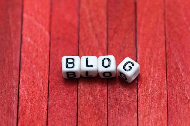 Blocchetti del cubo del blog organizzati su fondo di legno rosso
