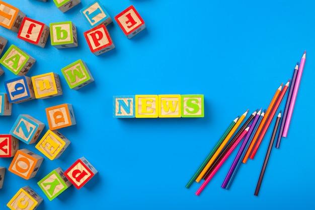 Blocchetti dell'alfabeto variopinto di superficie di legno di notizie su blu, disposizione piana, vista superiore