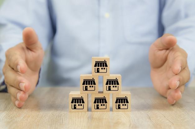 Blocchetti di legno del giocattolo della mano e del cubo del primo piano impilati in piramide con l'icona del negozio di affari di franchising.