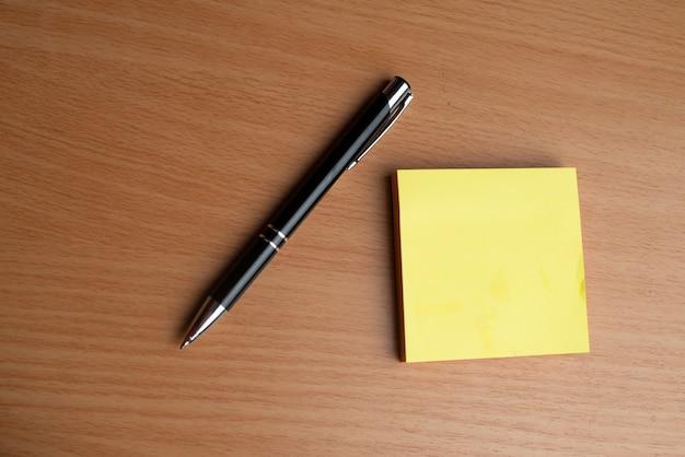 Blocchetti per appunti gialli con la penna nera sulla tavola di legno