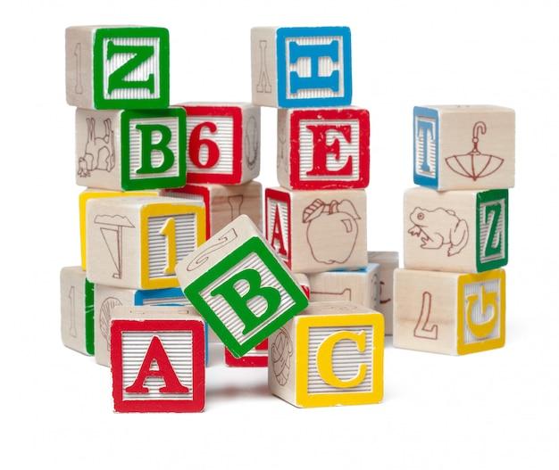 Blocchetti variopinti di alfabeto impilati in un disordine isolato su bianco