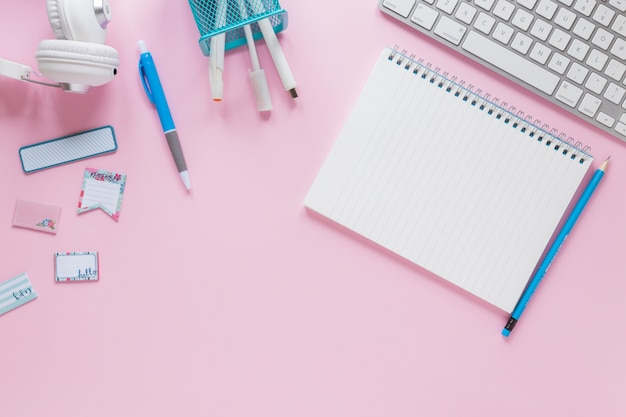 Blocchetto per appunti a spirale in bianco con le cancellerie e tastiera su fondo rosa