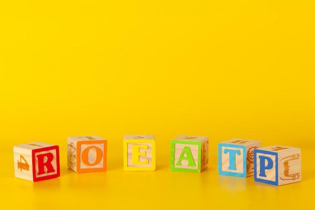 Blocchi di legno colorati con lettere su uno sfondo di colore giallo