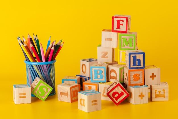 Blocchi di legno colorati e tazza con matite colorate su giallo