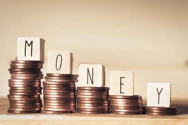 Blocchi di legno con i soldi di parola e un mucchio di monete, scale rampicanti dei soldi, concetto di affari