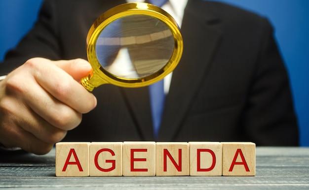 Blocchi di legno con la parola agenda e uomo d'affari. elenco delle domande alla riunione.