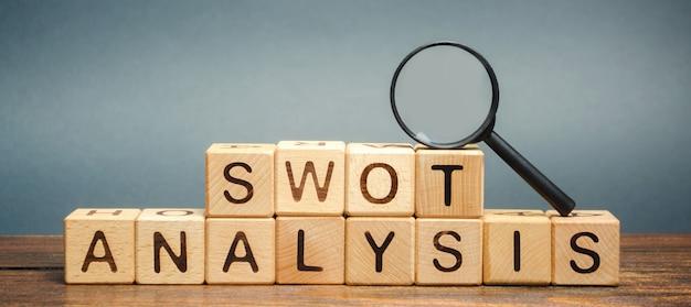 Blocchi di legno con la parola analisi swot e una lente d'ingrandimento.