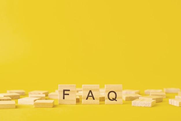 Blocchi di legno con la parola faq su sfondo giallo