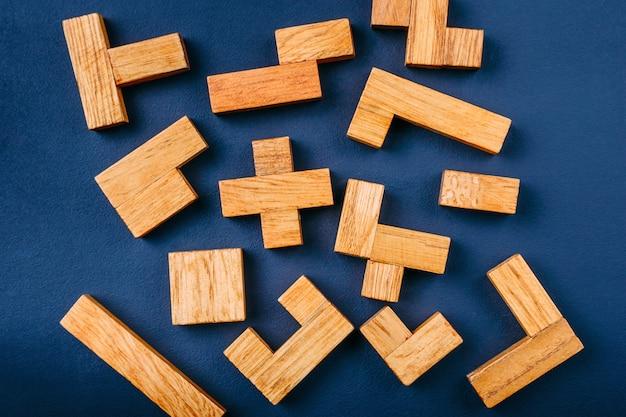 Blocchi di legno di forme geometriche differenti su uno sfondo scuro.