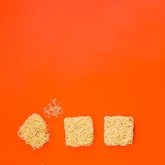 Blocchi di spaghetti istantanei disposti su una superficie arancione brillante