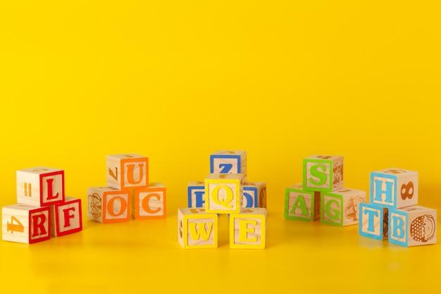 Blocchi di superficie in legno colorati con lettere su un colore giallo