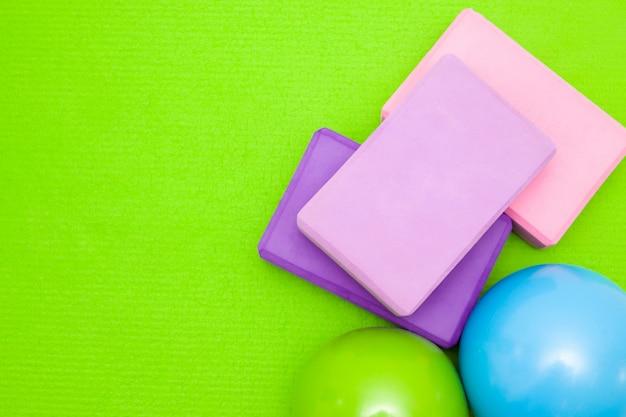 Blocchi rosa e viola, palline e manubri sul tappetino verde.