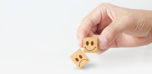Blocco cubo in mano con l'icona della faccia felice e triste